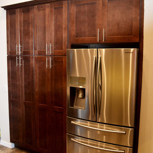 Medium sized contemporary u-shaped kitchen pantry in Tampa with a belfast sink, shaker cabinets, brown cabinets, granite worktops, beige splashback, glass tiled splashback, stainless steel appliances, porcelain flooring and a breakfast bar.