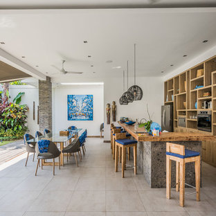 Design ideas for a tropical galley open plan kitchen in Perth with open cabinets, medium wood cabinets, wood benchtops, stainless steel appliances, a peninsula, grey floor and brown benchtop.