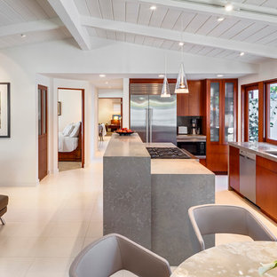 This is an example of a small midcentury galley open plan kitchen in Santa Barbara with an undermount sink, flat-panel cabinets, medium wood cabinets, limestone benchtops, grey splashback, stainless steel appliances, limestone floors and with island.