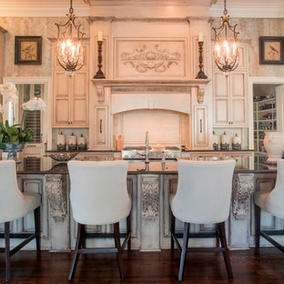 Design ideas for a victorian kitchen in New Orleans with raised-panel cabinets, beige cabinets, panelled appliances, dark hardwood floors and with island.