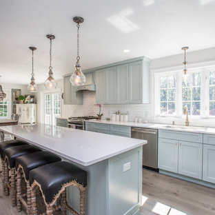 Large transitional eat-in kitchen ideas - Example of a large transitional l-shaped light wood floor and beige floor eat-in kitchen design in Boston with an undermount sink, shaker cabinets, blue cabinets, quartzite countertops, white backsplash, stone tile backsplash, stainless steel appliances and an island
