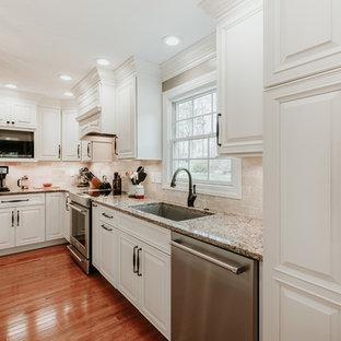 Mittelgroße Klassische Wohnküche in L-Form mit Unterbauwaschbecken, profilierten Schrankfronten, weißen Schränken, Granit-Arbeitsplatte, Küchenrückwand in Braun, Rückwand aus Travertin, Küchengeräten aus Edelstahl, hellem Holzboden, Kücheninsel und brauner Arbeitsplatte in Sonstige