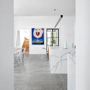 メルボルンの中サイズのカントリー風おしゃれなキッチン (ダブルシンク、フラットパネル扉のキャビネット、白いキャビネット、クオーツストーンカウンター、白いキッチンパネル、大理石の床、白い調理設備、コンクリートの床、白い床、白いキッチンカウンター) の写真