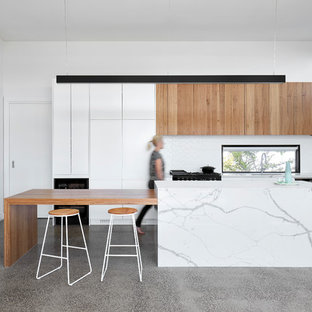 Photo of a mid-sized country l-shaped open plan kitchen in Melbourne with flat-panel cabinets, white cabinets, quartz benchtops, white splashback, marble splashback, concrete floors, with island, white benchtop, panelled appliances and grey floor.