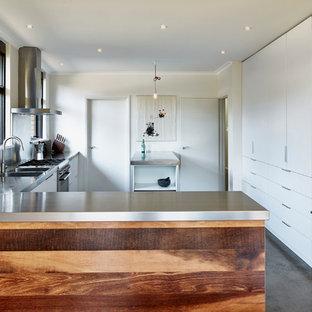 Ejemplo de cocina en L, actual, de tamaño medio, con fregadero integrado, armarios con paneles lisos, puertas de armario blancas, encimera de acero inoxidable, electrodomésticos de acero inoxidable, suelo de cemento y península