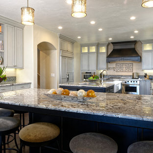 This is an example of a mid-sized midcentury u-shaped open plan kitchen in Denver with a farmhouse sink, shaker cabinets, beige cabinets, granite benchtops, beige splashback, subway tile splashback, panelled appliances, dark hardwood floors and multiple islands.