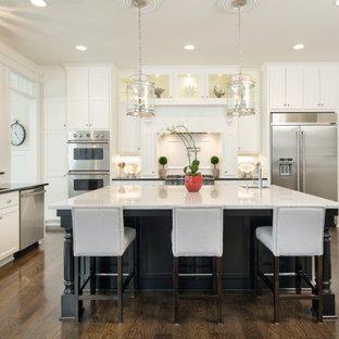 Transitional kitchen remodeling - Example of a transitional u-shaped dark wood floor and brown floor kitchen design in Kansas City with an undermount sink, shaker cabinets, white cabinets, stainless steel appliances, an island and white countertops
