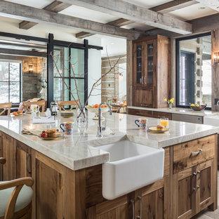 ジャクソンのラスティックスタイルのおしゃれなアイランドキッチン (エプロンフロントシンク、シェーカースタイル扉のキャビネット、中間色木目調キャビネット、大理石カウンター、ベージュのキッチンカウンター、グレーの床) の写真