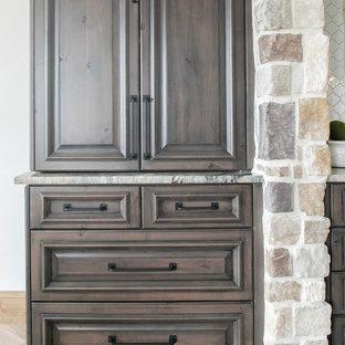 Idéer för ett mycket stort medelhavsstil grå kök, med luckor med upphöjd panel, skåp i mörkt trä, bänkskiva i kvartsit, vitt stänkskydd, stänkskydd i keramik, rostfria vitvaror, ljust trägolv och flera köksöar
