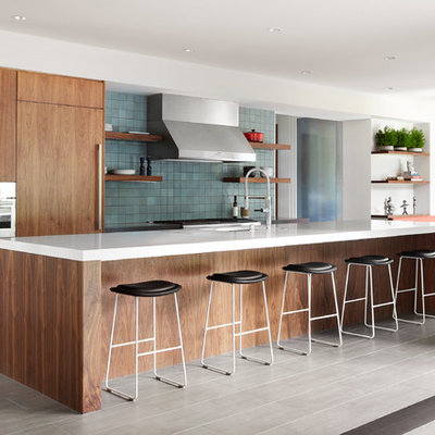 Huge trendy galley porcelain tile and gray floor eat-in kitchen photo in San Francisco with an undermount sink, flat-panel cabinets, quartz countertops, blue backsplash, ceramic backsplash, an island, medium tone wood cabinets, paneled appliances and white countertops