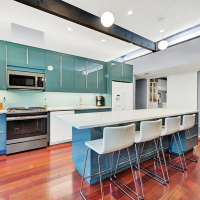 Mid-sized trendy galley medium tone wood floor and brown floor kitchen photo in Sacramento with quartz countertops, glass sheet backsplash, an undermount sink, flat-panel cabinets, green cabinets, green backsplash, white appliances and an island