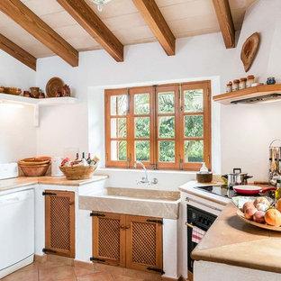 Ispirazione per una cucina ad U mediterranea di medie dimensioni con nessuna isola, nessun'anta, pavimento in terracotta e top marrone