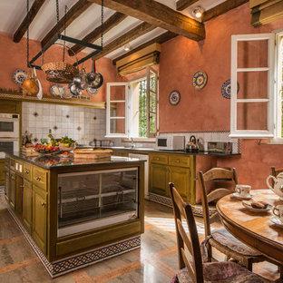 Imagen de cocina comedor en L, rural, grande, con armarios con paneles con relieve, puertas de armario verdes, salpicadero blanco, electrodomésticos blancos, una isla y suelo de mármol