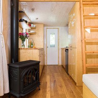 ロサンゼルスの小さいコンテンポラリースタイルのおしゃれなキッチン (シングルシンク、フラットパネル扉のキャビネット、淡色木目調キャビネット、木材カウンター、シルバーの調理設備、無垢フローリング、アイランドなし) の写真