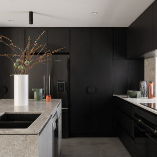 Inspiration for a large modern l-shaped kitchen in Perth with an undermount sink, black cabinets, granite benchtops, window splashback, black appliances, concrete floors, with island, grey floor, grey benchtop and flat-panel cabinets.