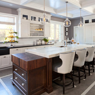 Example of a large transitional l-shaped ceramic floor and gray floor eat-in kitchen design in Denver with a farmhouse sink, shaker cabinets, white cabinets, marble countertops, white backsplash, ceramic backsplash, paneled appliances and an island