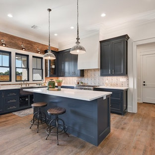Coastal kitchen pictures - Beach style medium tone wood floor and brown floor kitchen photo in New Orleans with shaker cabinets, blue cabinets, an island and white countertops