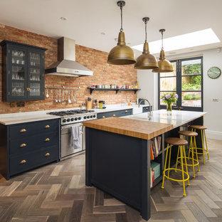 ロンドンの中サイズのトランジショナルスタイルのおしゃれなキッチン (エプロンフロントシンク、フラットパネル扉のキャビネット、青いキャビネット、茶色い床、茶色いキッチンパネル、レンガのキッチンパネル、シルバーの調理設備の、無垢フローリング) の写真