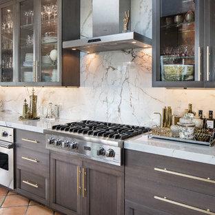 Esempio di una grande cucina eclettica con lavello da incasso, ante di vetro, ante grigie, top in marmo, paraspruzzi bianco, paraspruzzi in lastra di pietra, elettrodomestici in acciaio inossidabile, pavimento in terracotta e isola