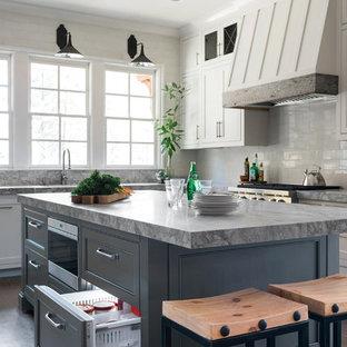 アトランタのトラディショナルスタイルのおしゃれなアイランドキッチン (シェーカースタイル扉のキャビネット、白いキャビネット、白いキッチンパネル、シルバーの調理設備、濃色無垢フローリング) の写真