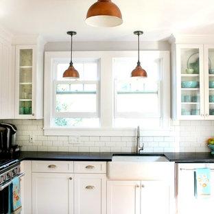 Diseño de cocina en U, campestre, pequeña, cerrada, con fregadero sobremueble, armarios estilo shaker, puertas de armario blancas, encimera de esteatita, salpicadero blanco, salpicadero de azulejos tipo metro, electrodomésticos de acero inoxidable y suelo de madera en tonos medios