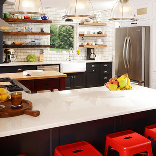 Mid-sized farmhouse eat-in kitchen pictures - Example of a mid-sized country u-shaped light wood floor eat-in kitchen design in Other with a farmhouse sink, recessed-panel cabinets, black cabinets, white backsplash, subway tile backsplash, stainless steel appliances, an island and solid surface countertops
