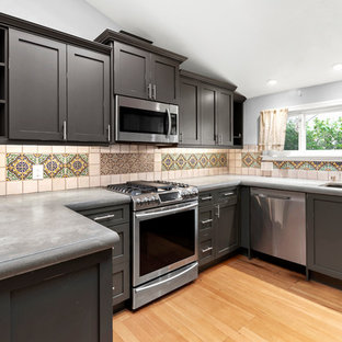 Photo of a small traditional u-shaped kitchen in San Francisco with an undermount sink, shaker cabinets, distressed cabinets, concrete benchtops, ceramic splashback, stainless steel appliances, medium hardwood floors, brown floor and grey benchtop.