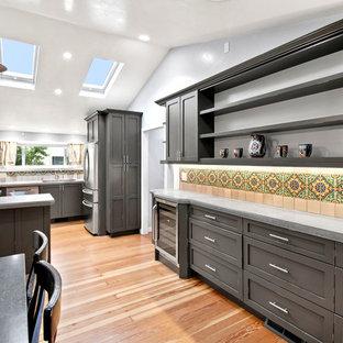 サンフランシスコの小さいシャビーシック調のおしゃれなコの字型キッチン (アンダーカウンターシンク、シェーカースタイル扉のキャビネット、ヴィンテージ仕上げキャビネット、コンクリートカウンター、セラミックタイルのキッチンパネル、シルバーの調理設備の、無垢フローリング、茶色い床、グレーのキッチンカウンター) の写真