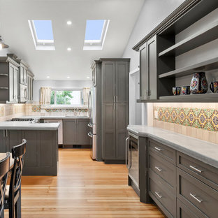This is an example of a small traditional u-shaped kitchen in San Francisco with an undermount sink, shaker cabinets, distressed cabinets, concrete benchtops, ceramic splashback, stainless steel appliances, medium hardwood floors, brown floor and grey benchtop.