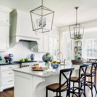 Immagine di una cucina abitabile chic con lavello sottopiano, ante in stile shaker, ante bianche, paraspruzzi bianco, paraspruzzi con piastrelle diamantate, elettrodomestici in acciaio inossidabile, pavimento in legno massello medio e isola