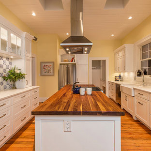 Inspiration for a large country galley kitchen pantry in Other with a belfast sink, shaker cabinets, white cabinets, wood worktops, white splashback, mosaic tiled splashback, stainless steel appliances, medium hardwood flooring, an island and orange floors.