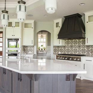Large transitional open concept kitchen pictures - Example of a large transitional l-shaped dark wood floor and brown floor open concept kitchen design in Minneapolis with a farmhouse sink, shaker cabinets, white cabinets, quartz countertops, multicolored backsplash, cement tile backsplash, paneled appliances and an island