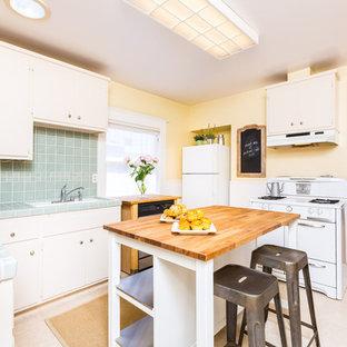 Amerikansk inredning av ett avskilt, litet turkos turkost u-kök, med släta luckor, vita skåp, kaklad bänkskiva, blått stänkskydd, stänkskydd i keramik, vita vitvaror och en köksö