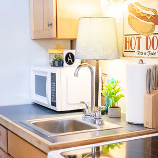 アルバカーキの小さいエクレクティックスタイルのおしゃれなキッチン (ドロップインシンク、シェーカースタイル扉のキャビネット、淡色木目調キャビネット、ラミネートカウンター、白い調理設備、コンクリートの床、アイランドなし、緑の床、青いキッチンカウンター) の写真