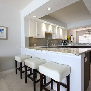 This is an example of a mid-sized beach style u-shaped open plan kitchen in Tampa with an undermount sink, recessed-panel cabinets, granite benchtops, grey splashback, glass tile splashback, stainless steel appliances, marble floors, a peninsula and white cabinets.
