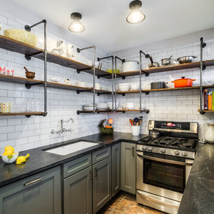 Design ideas for a small industrial l-shaped kitchen in Chicago with an undermount sink, shaker cabinets, grey cabinets, granite benchtops, white splashback, subway tile splashback, no island, stainless steel appliances, slate floors and brown floor.