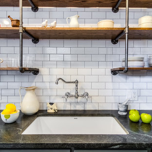 Small industrial galley separate kitchen in Chicago with an undermount sink, shaker cabinets, grey cabinets, white splashback, subway tile splashback, no island, soapstone benchtops, stainless steel appliances, slate floors and brown floor.