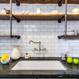 シカゴの小さいインダストリアルスタイルのおしゃれなキッチン (アンダーカウンターシンク、シェーカースタイル扉のキャビネット、グレーのキャビネット、白いキッチンパネル、サブウェイタイルのキッチンパネル、アイランドなし、ソープストーンカウンター、シルバーの調理設備の、スレートの床、茶色い床) の写真