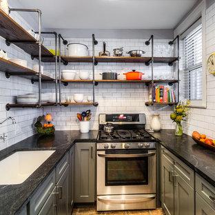 シカゴの小さいインダストリアルスタイルのおしゃれなキッチン (アンダーカウンターシンク、シェーカースタイル扉のキャビネット、グレーのキャビネット、白いキッチンパネル、サブウェイタイルのキッチンパネル、アイランドなし、シルバーの調理設備の、ソープストーンカウンター、スレートの床、茶色い床) の写真