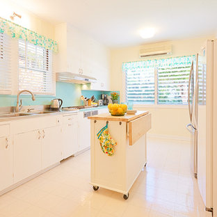 Design ideas for a large tropical galley separate kitchen in Hawaii with a double-bowl sink, flat-panel cabinets, white cabinets, laminate benchtops, blue splashback, stainless steel appliances, vinyl floors and with island.