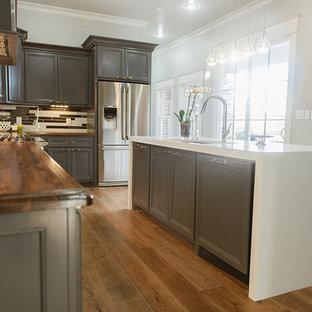 ダラスの中サイズのエクレクティックスタイルのおしゃれなキッチン (アンダーカウンターシンク、シェーカースタイル扉のキャビネット、グレーのキャビネット、木材カウンター、マルチカラーのキッチンパネル、ボーダータイルのキッチンパネル、シルバーの調理設備、淡色無垢フローリング) の写真