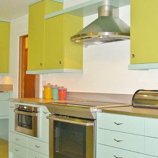 ポートランドの中サイズのミッドセンチュリースタイルのおしゃれなキッチン (ドロップインシンク、フラットパネル扉のキャビネット、緑のキャビネット、ラミネートカウンター、メタリックのキッチンパネル、シルバーの調理設備の、クッションフロア、アイランドなし) の写真
