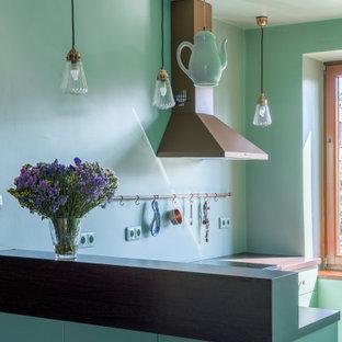 На фото: с высоким бюджетом угловые кухни-гостиные среднего размера в стиле ретро с монолитной раковиной, плоскими фасадами, зелеными фасадами, деревянной столешницей, зеленым фартуком, черной техникой, полом из цементной плитки, полуостровом, зеленым полом и коричневой столешницей