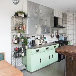 ロンドンの大きいエクレクティックスタイルのおしゃれなアイランドキッチン (緑のキャビネット、ステンレスカウンター、コンクリートの床、グレーのキッチンカウンター、フラットパネル扉のキャビネット、白いキッチンパネル、黒い調理設備、グレーの床) の写真