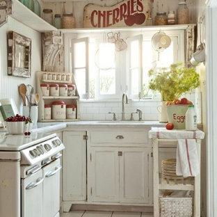 Geschlossene Shabby-Look Küche mit Schränken im Used-Look, Küchenrückwand in Weiß, Rückwand aus Metrofliesen und weißen Elektrogeräten in Los Angeles
