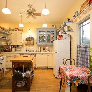Réalisation d'une petite cuisine style shabby chic en L fermée avec un évier encastré, un placard à porte shaker, des portes de placard blanches, un plan de travail en carrelage, une crédence blanche, une crédence en bois, un électroménager blanc, un sol en bois clair, un îlot central et un sol marron.