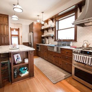 シーダーラピッズのヴィクトリアン調のおしゃれなキッチン (エプロンフロントシンク、インセット扉のキャビネット、中間色木目調キャビネット、御影石カウンター、白いキッチンパネル、サブウェイタイルのキッチンパネル、シルバーの調理設備の、無垢フローリング) の写真