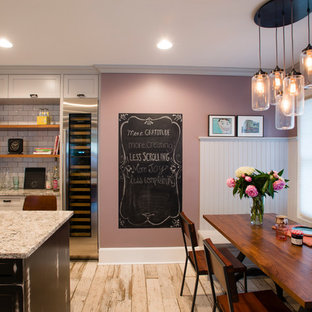 Photo of a large country l-shaped eat-in kitchen in New York with a farmhouse sink, recessed-panel cabinets, distressed cabinets, quartz benchtops, white splashback, subway tile splashback, stainless steel appliances, ceramic floors and with island.