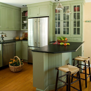 Mid-sized traditional eat-in kitchen ideas - Eat-in kitchen - mid-sized traditional u-shaped medium tone wood floor eat-in kitchen idea in Boston with a farmhouse sink, recessed-panel cabinets, green cabinets, soapstone countertops, white backsplash, ceramic backsplash, stainless steel appliances and black countertops