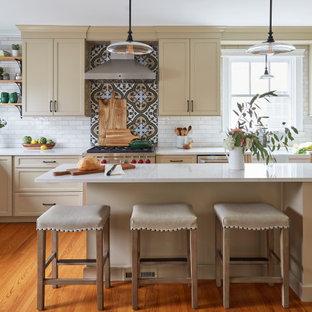 Klassische Wohnküche in U-Form mit Landhausspüle, Schrankfronten im Shaker-Stil, beigen Schränken, Quarzit-Arbeitsplatte, bunter Rückwand, Rückwand aus Porzellanfliesen, Küchengeräten aus Edelstahl, braunem Holzboden, Kücheninsel und beiger Arbeitsplatte in Chicago